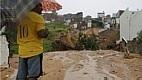 Homem observa cratera aberta em rua de Natal. Chuvas castigam a cidade que ainda recebe três jogos da Copa do Mundo