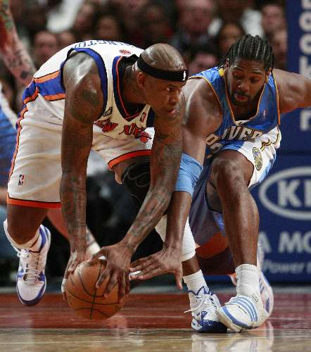 Al Harrington, do New York Knicks, tenta manter a posse da bola contra Nenê, do Denver Nuggets