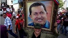 Venezuelano carrega quadro de Chávez em marcha homenageando o líder dois anos após sua morte - AP