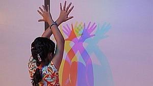 Menina brinca com a projeção de feixes de luz - Anita Évola