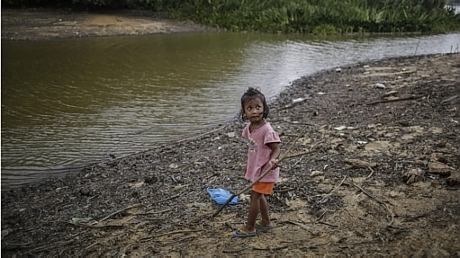 Menina brinca na margem do Lago de Bukit Merah Taiiping, em Perak, na Malásia. A situação é crítica por causa dos danos causados pelo fenômeno meteorológico El Niño  - Fazry Ismail/EFE