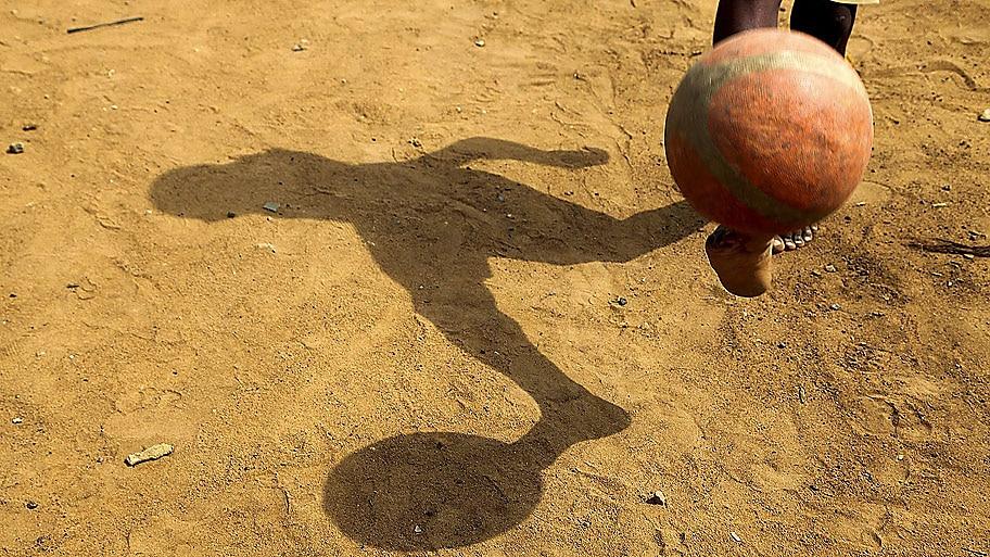 Legnan Koula/EFE - Menino joga futebol em campo de terra de Abidjan, na Costa do Marfim Foto: Legnan Koula/EFE