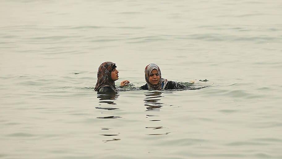 Mohammed Salem/Reuters - Mulheres palestinas nadando de roupa no mar Mediterrâneo, na costa de Gaza. Foto:Mohammed Salem/Reuters