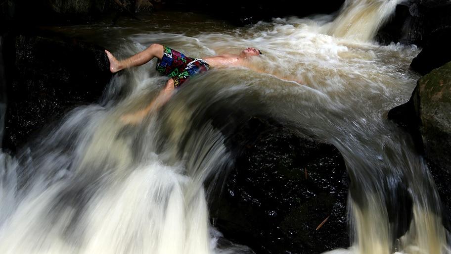 - Turista tenta espantar o calor numa das cachoeiras da Serra da Mantiqueira, no interior de São Paulo. Foto: Hélvio Romero / Estadão