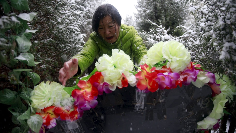 - Zheng Qing chora ao mostrar o túmulo de seu filho no cemitério em Zhangjiakou, na China. Campanha pede apoio financeiro e moral àqueles cujo único filho morreu. Foto: Kim Kyung-Hoon / Reuters