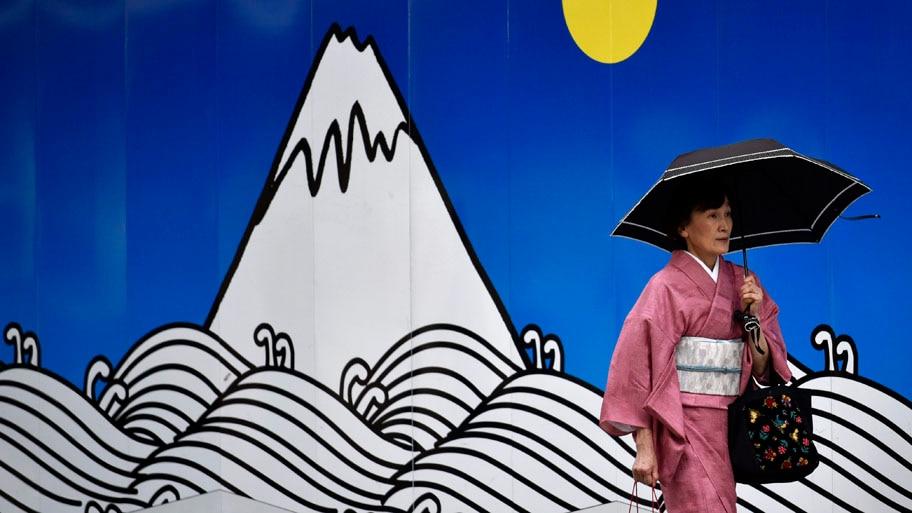 - Uma mulher passa em frente a um mural no distrito comercial de Ginza, em Tóquio, Japão. Foto: Franck Robichon / EFE
