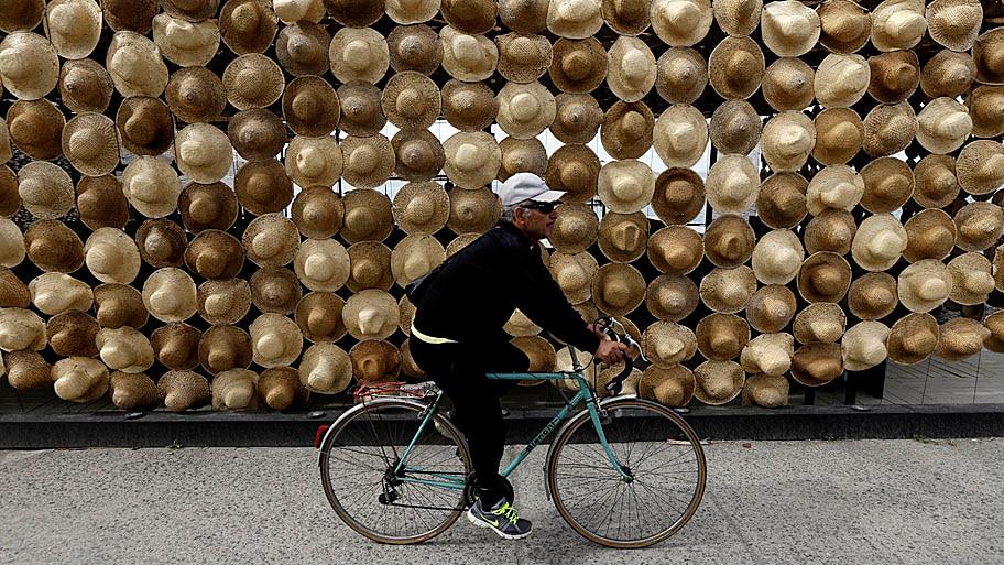 Thanassis Stavrakis/AP - Ciclista passa em frente a um vendedor de chapéus na praia de Kalamata, na Grécia. Foto: Thanassis Stavrakis/AP