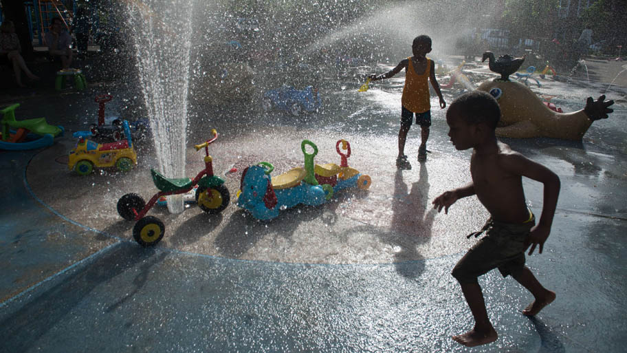 - Crianças se refrescam brincando com água em praça no bairro do Brooklyn, em Nova York. Foto: Stephanie Keith/AFP