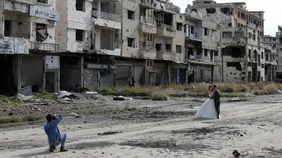 - Recém-casados tiram fotos em meio à destruição da cidade de Homs, na Síria. Foto: Joseph Eid/AFP