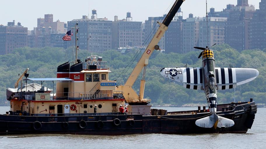 - Avião modelo P-47 Thunderbolt  da Segunda Guerra sendo retirado do Rio Hudson, em Nova York,  após ter caído nessa sexta-feira. Um corpo que seria do piloto foi encontrado na aeronave. Foto: Julio Cortez/AP