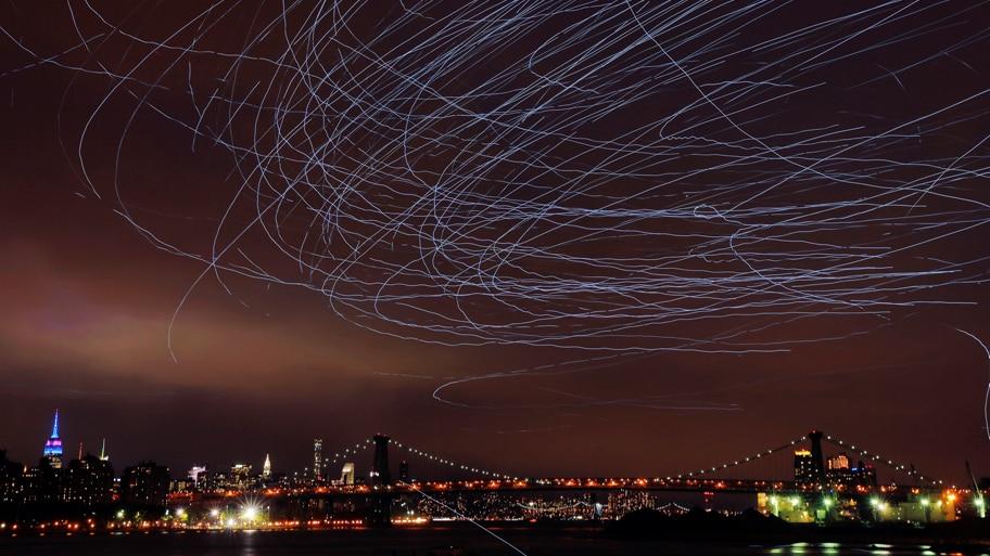 - Os pombos com as luzes de LED voam sobre o Brooklyn, Nova York , criando rastros de luz. Foto: Michael Reaves/AFP