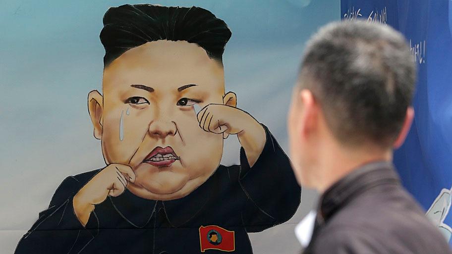 Lee Jin-man/AP - Homem olha para uma caricatura do líder norte-coreano Kim Jong Un, durante a Expo Unificação, no centro de Seul. Foto: Lee Jin-man/AP