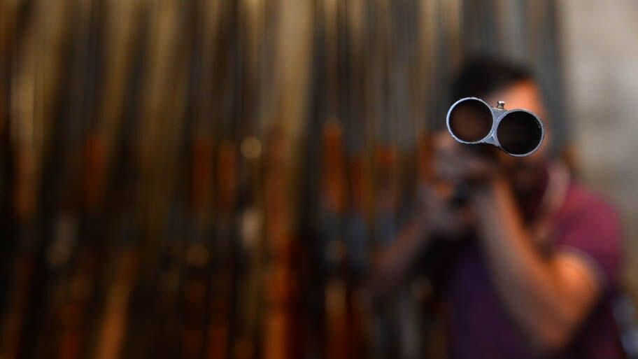 - Homem testa rifle em fábrica de armas de Srinagar, na Índia. Foto: Tauseef Mustafa/AFP