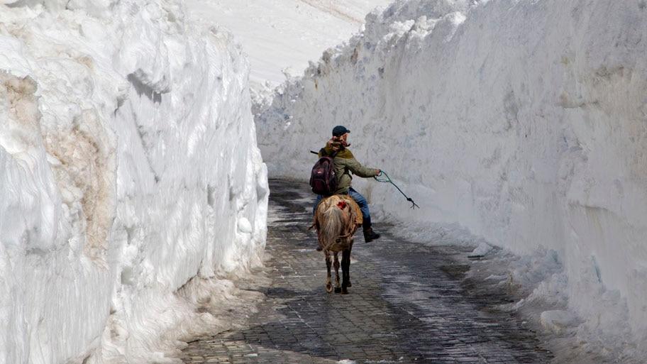 - Homem anda a cavalo entre paredes de neve, na passagem Zojila, ao norte de Srinagar, na Caxemira indiana. A estrada atravessa uma região próxima a Cordilheira do Himalaia. Foto: Dar Yasin / AP