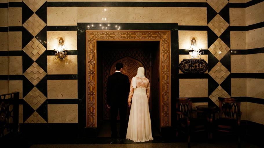 Hassan Ammar/AP - Uma casal de noivos egípcios preparam-se para entrar em salão, para assinar seu contrato de casamento religioso, no Cairo, Egito. Credito: Hassan Ammar/AP