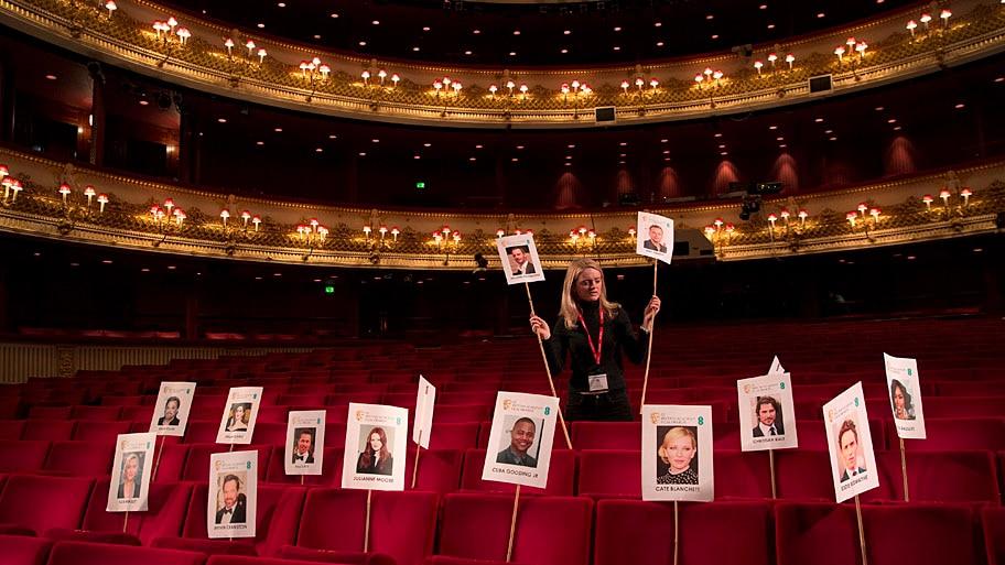 - Membro da equipe do Royal Opera House, em Londres, coloca fotos sobre os assentos do teatro, em preparação para a festa de premiação que acontecerá no próximo domingo. Foto: Joel Ryan / Invision / AP