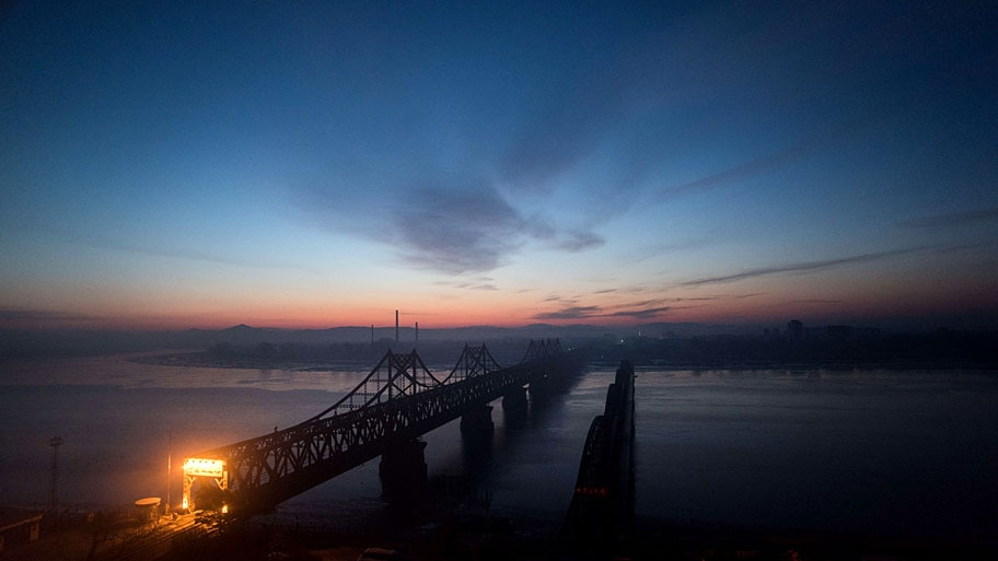 - O sol nasce sobre o Rio Yalu na cidade chinesa de Dandong, vizinha a norte-coreana Sinuiju, na manhã de hoje. A Coreia do Norte religou um reator que poderia começar a recuperar material para arma nucleares. Foto: Joha nnes Eisele / AFP