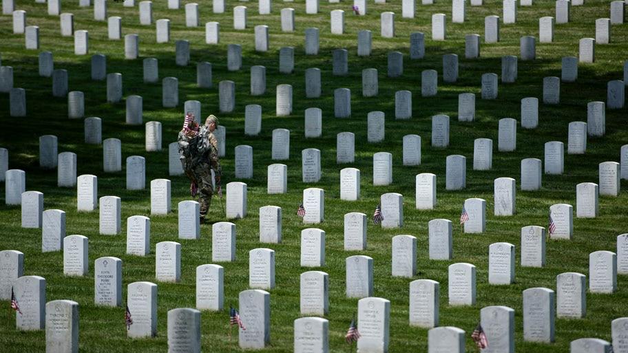 - Soldado leva bandeiras entre as sepulturas do cemitério nacional de Arlington, na Virginia. Foto: Brendan Smialowski / AFP