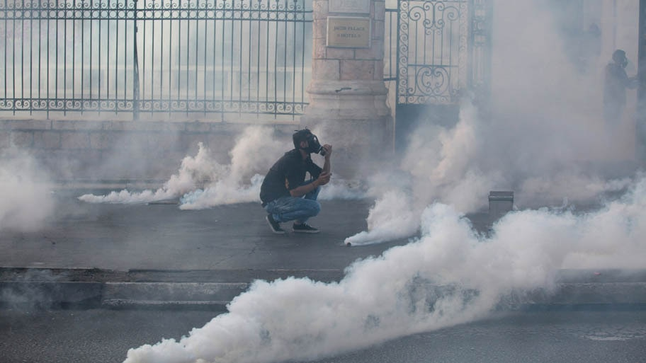 - Palestino se protege de bombas de  gás lacrimogêneo em confronto com tropas israelenses em Bethlehem. Foto: Abdelrahman Younis/Reuters
