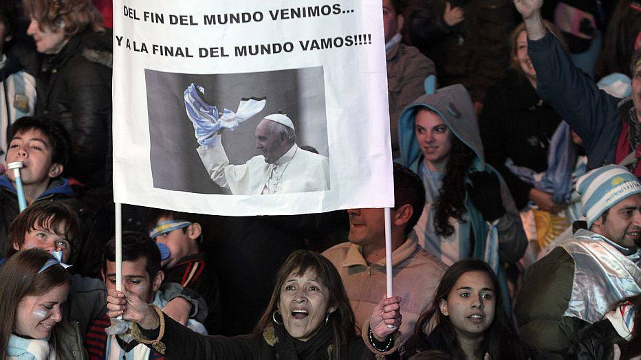 """Argentine fans celebrate in Buenos Aires on July 9, 2014, after beating the Netherlands in their FIFA World Cup semi-final football match. Argentina beat the Netherlands 4-2 in penalty kicks and will now face Germany in the World Cup final. The banner portrays Pope Francis and reads, """"We come from the end of the world... And we're going to the world cup finals"""