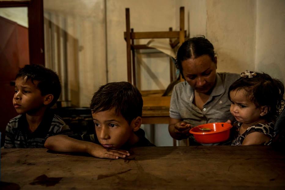 Pais alimentam filhos em Caracas