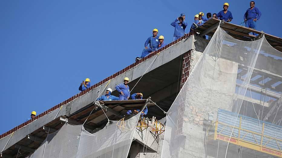 Operários de uma construção em frente ao estádio pararam o trabalho para tentar assistir um pouco do treino da seleção brasileira.