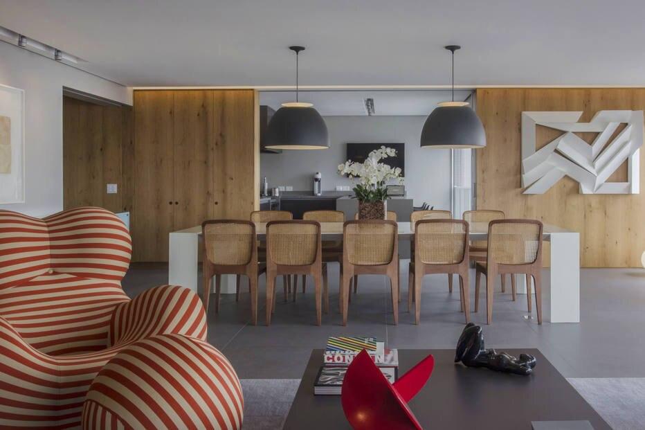 Além de servir como moldura para o mobiliário e a decoração, a madeira conduz o olhar pelos diferentes espaços deixando o projeto linear
