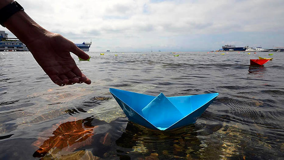A resident launches a paper boat during celebrations for the 69th anniversary of the end of World War Two in the far eastern city of Vladivostok, September 2, 2014. The holiday, marking the victory over Japan in World War II, is a Russian national memorial day, established by then President Dmitry Medvedev and approved by the Russian State Duma and the Federation Council on July 23, 2010.  REUTERS/Yuri Maltsev (RUSSIA - Tags: POLITICS ANNIVERSARY CONFLICT)