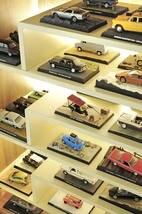 Detalhe de carrinhos de coleção organizados em estante na sala de TV
