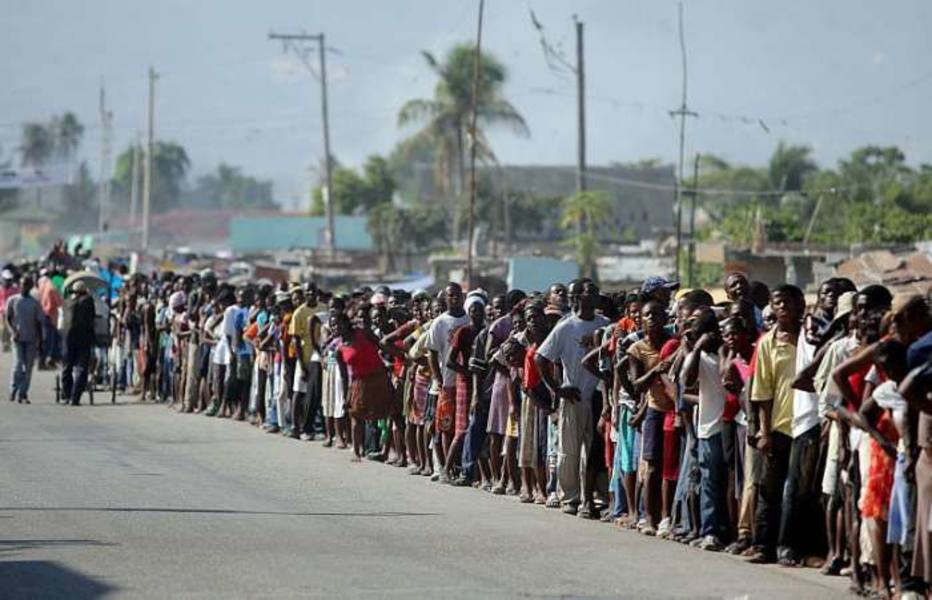 Haitianos fazem fila para receber alimentos do Exército brasileiro