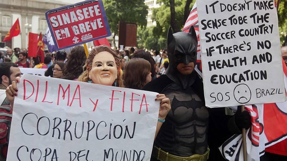No Rio de Janeiro pessoas seguram cartazes contra Dilma Rousseff e a FIFA