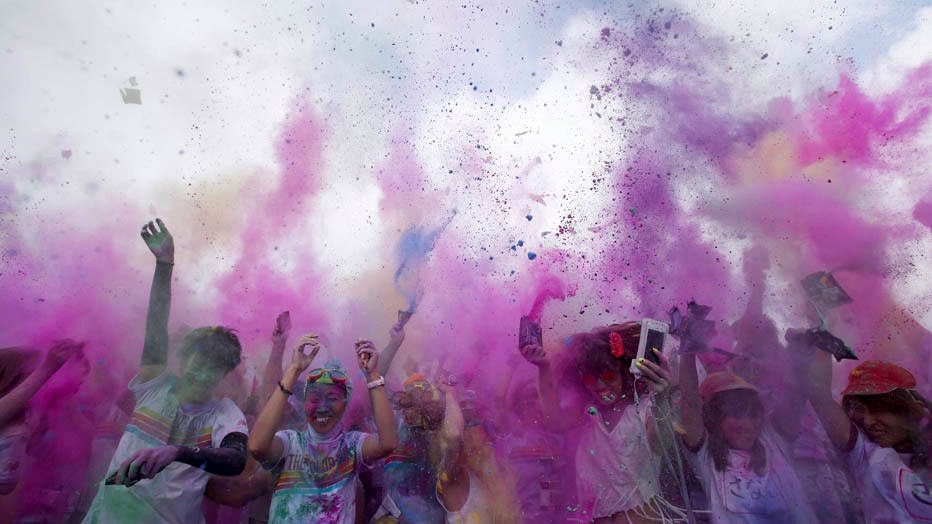 Some of the over 6,000 participants in the Color Run 5 kilometers, celebrate at the finish line by simultaneously throwing colored powder in the air in Susono, at the foot of Mt. Fuji, southwest of Tokyo Saturday, Sept. 6, 2014. (AP Photo/Eugene Hoshiko)