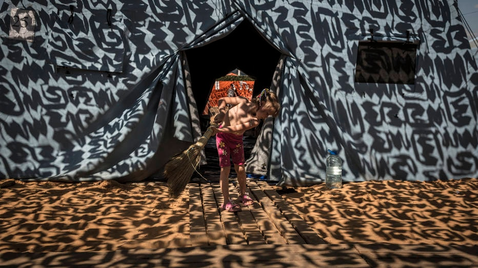 Under the shade of a camouflage netting, a girl sweeps sand from the entrance to her tent at a refugee camp in Novoshakhtinsk, Russia, on the border with Ukraine, Aug. 23, 2014. Hundreds of thousands of Ukrainians displaced by war have accepted resettlement and are transport to cities all across Russia. Many say they aren�t coming back. (Sergey Ponomarev/The New York Times)