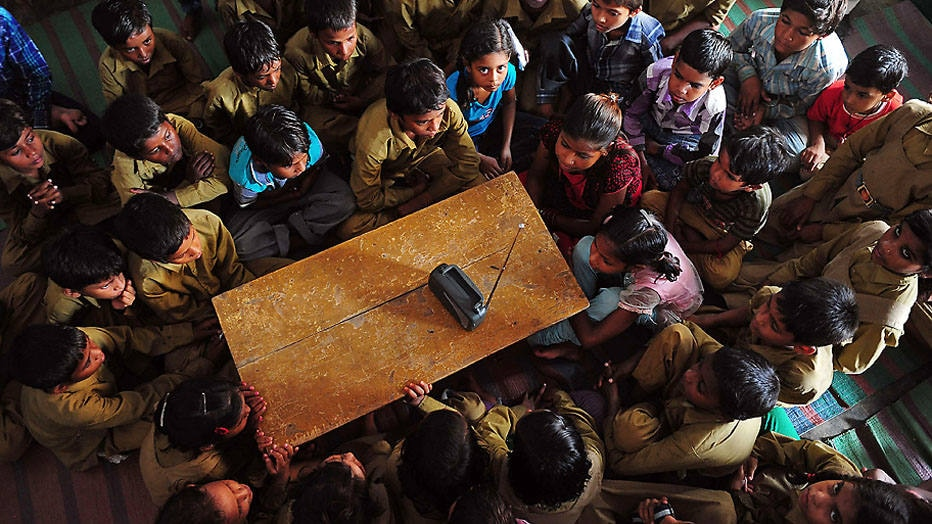 Indian schoolchildren crowd around a radio as they listen to a broadcast by Indian Prime Minister Narendra Modi delivering his Teachers' Day speech at a primary municipal school at Bakshi Kala Daraganj in Allahabad on September 5, 2014. Modi addressed hundreds of thousands of students during a live telecast to classrooms across India for the country's Teachers' Day celebrations, which coincides with the birthday of India's second president and eminent academician Sarvapalli Radhakrishnan. AFP PHOTO/SANJAY KANOJIA
