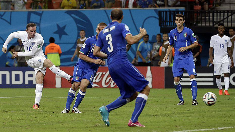 England's Wayne Rooney, left, drags his shot wide through the Italian defenders during the group D World Cup soccer match between England and Italy at the Arena da Amazonia in Manaus, Brazil, Saturday, June 14, 2014.  (AP Photo/Martin Mejia)
