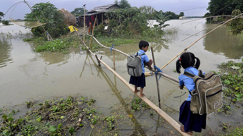 Indian schoolchildren use a bamboo bridge to cross floodwaters in Morkata village in the Morigoan district of Assam on August 25, 2014. Floods and landslides in Nepal and India have killed nearly 200 people and scores more are missing. Hundreds die every year in floods and landslides during the monsoon season in South Asia.  AFP PHOTO / Biju Boro