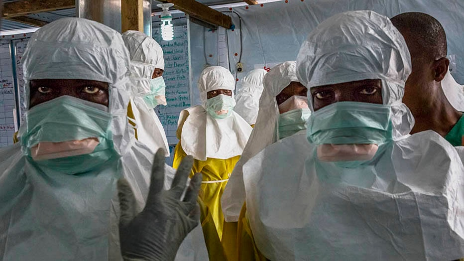 Health workers don protective clothing before entering a high-risk area at the Elwa Hospital in Monrovia, Liberia, Aug. 23, 2014. The epidemic has exposed gaping holes in the ability of health agencies, like the World Health Organization, to tackle outbreaks in an increasingly interconnected world, where diseases can quickly spread from remote villages to cities housing millions of people. (Daniel Berehulak/The New York Times)
