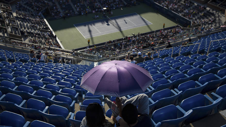 A pair of fans in nosebleed seats beat the heat with an umbrella during a match in Arthur Ashe Stadium on the first day of the U.S. Open, at the USTA Billie Jean King National Tennis Center in New York, Aug. 25, 2014. (Damon Winter/The New York Times)