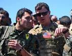 Soldado americano (D) conversa com combatente curdo das Unidades de Proteção do Povo (YPG) durante operação contra o Estado Islâmico na cidade síria de Derik