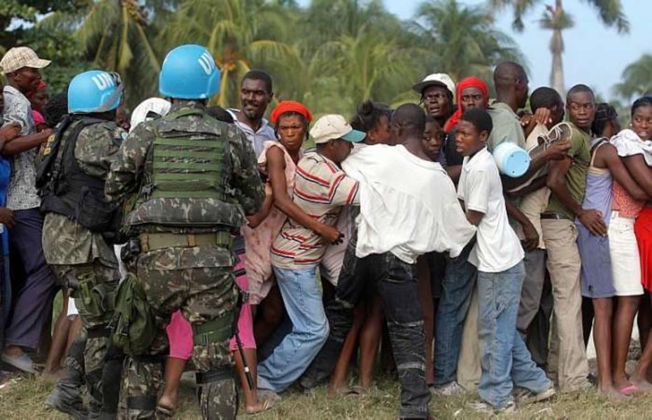 Exército brasileiro distribui alimentos para população em Cite Soleil, em Porto Príncipe