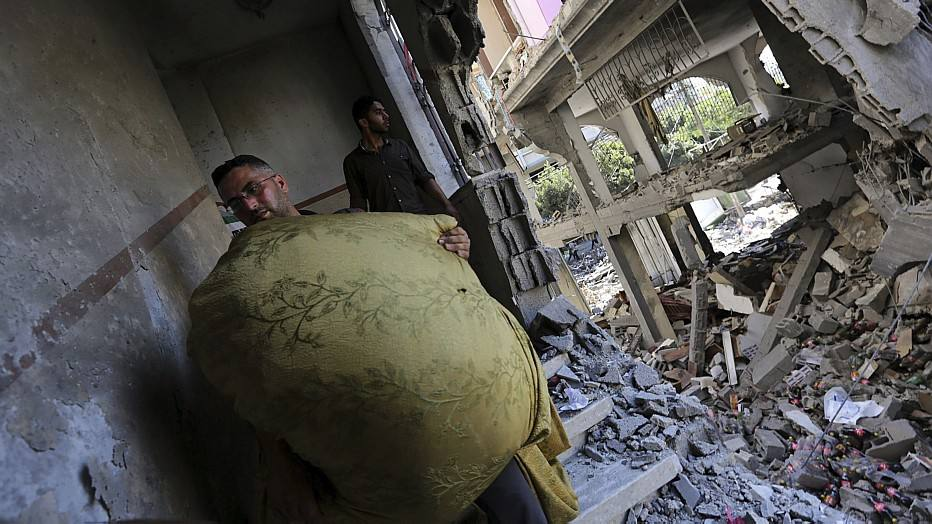 Membros da família Abu Lealla avaliam destroços de suas casas após bombardeio israelense que deixou 98 mortos e 600 feridos no norte de Gaza.