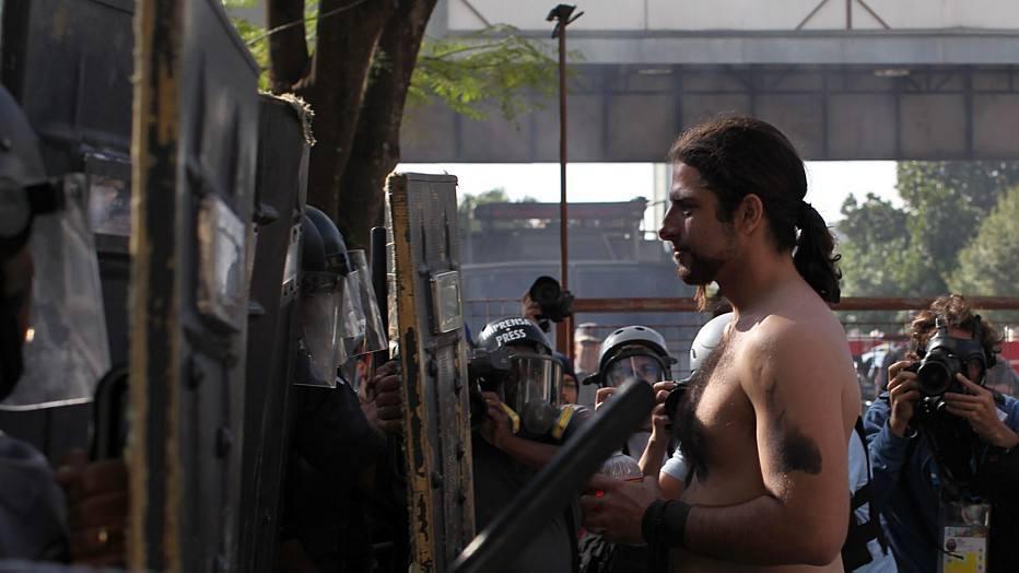 Um dos manifestantes fica frente a frente com a linha da tropa de choque. O protesto é contra os gastos públicos com a Copa do Mundo e em apoio aos metroviários demitidos durante a greve.