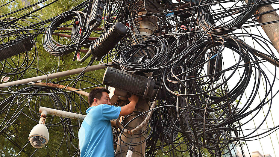 A worker makes repairs below electricity and communications cables on a pylon in Beijing on September 5, 2014. Shanghai stocks closed at a 17-month high on September 5 on hopes the Chinese government will introduce fresh measures to kickstart the world's number two economy. AFP PHOTO/Greg BAKER