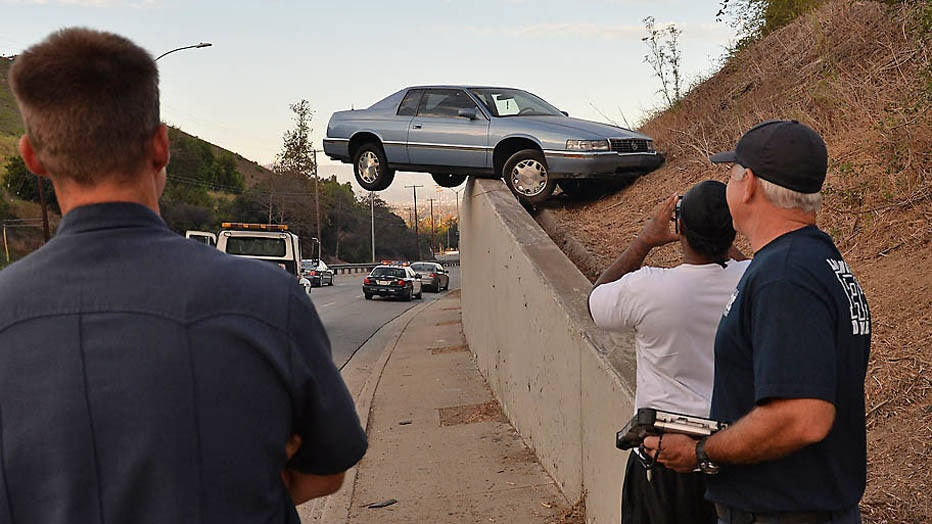 A car sits atop an embankment after losing control and skidding up the concrete retaining wall on South La Brea Ave in Baldwin Hills, Los Angeles on August 24, 2014. The driver and his passenger escaped injury.