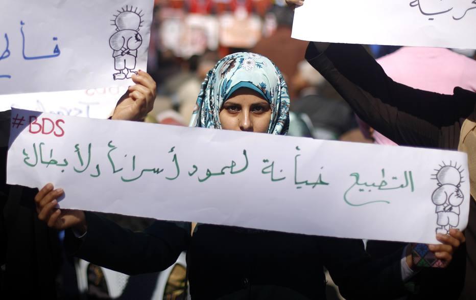 Palestinos protestam em frente ao escritório da Cruz Vermelha, na cidade de Gaza, pedindo a libertação de prisioneiros palestinos que estão emIsrael. Enunciado diz,em árabe: normalização é uma traição à resistência de nossos prisioneiros e heróis