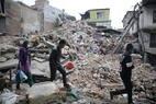 Pessoas transitam em meio a prédios caídos em Katmandu