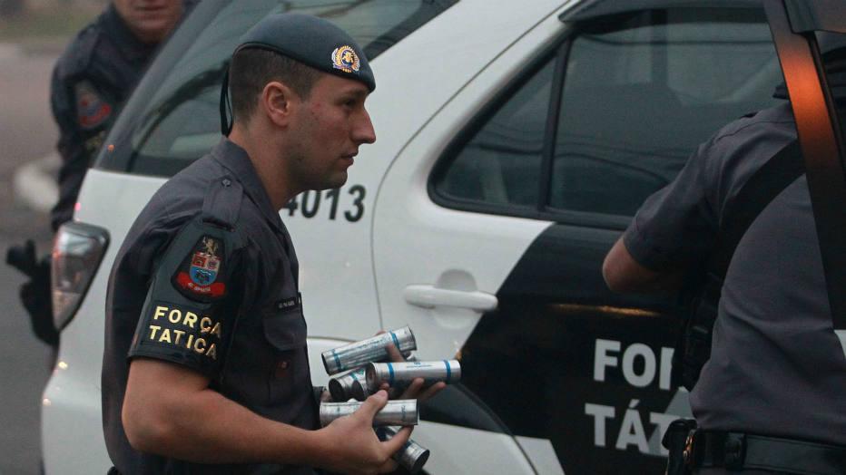 Policial carrega munição para enfrentar manifestantes. Durante a intervenção da Tropa de Choque, manifestantes se dispersaram pelas ruas da região e fizeram barricadas com objetos e lixeiras.