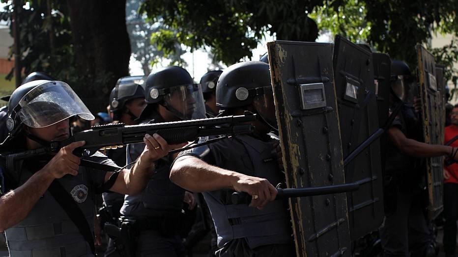 A Polícia Militar informou que só permitirá que o protesto fique restrito a um quarteirão da Rua Serra de Japi e que os manifestantes não podem marchar rumo à Arena Corinthians. Na foto, policial aponta arma para os manifestantes enquanto a tropa de choque avança para dispersar o protesto