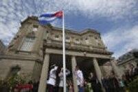 Oficiais cubanos batem continência à bandeira de Cuba hasteada na embaixada em Washington nesta segunda-feira, 20