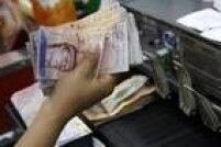 Caixa conta dinheiro em mercado de Caracas: inflação faz os venezuelanos levarem cada vez mais bolívares para as compras